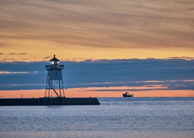 Grand Marais lighthouse and boat during blue hour after sunset