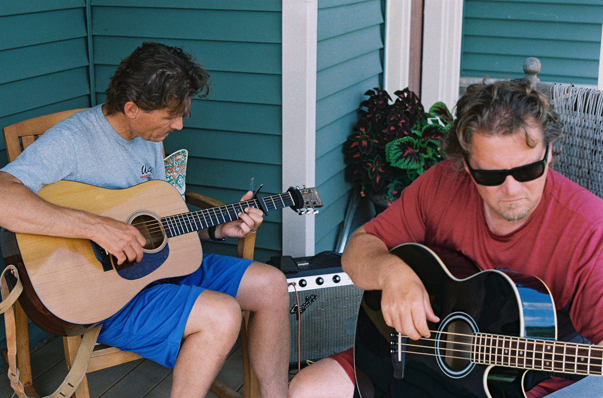 two musicians practicing on porch with guitar and bass